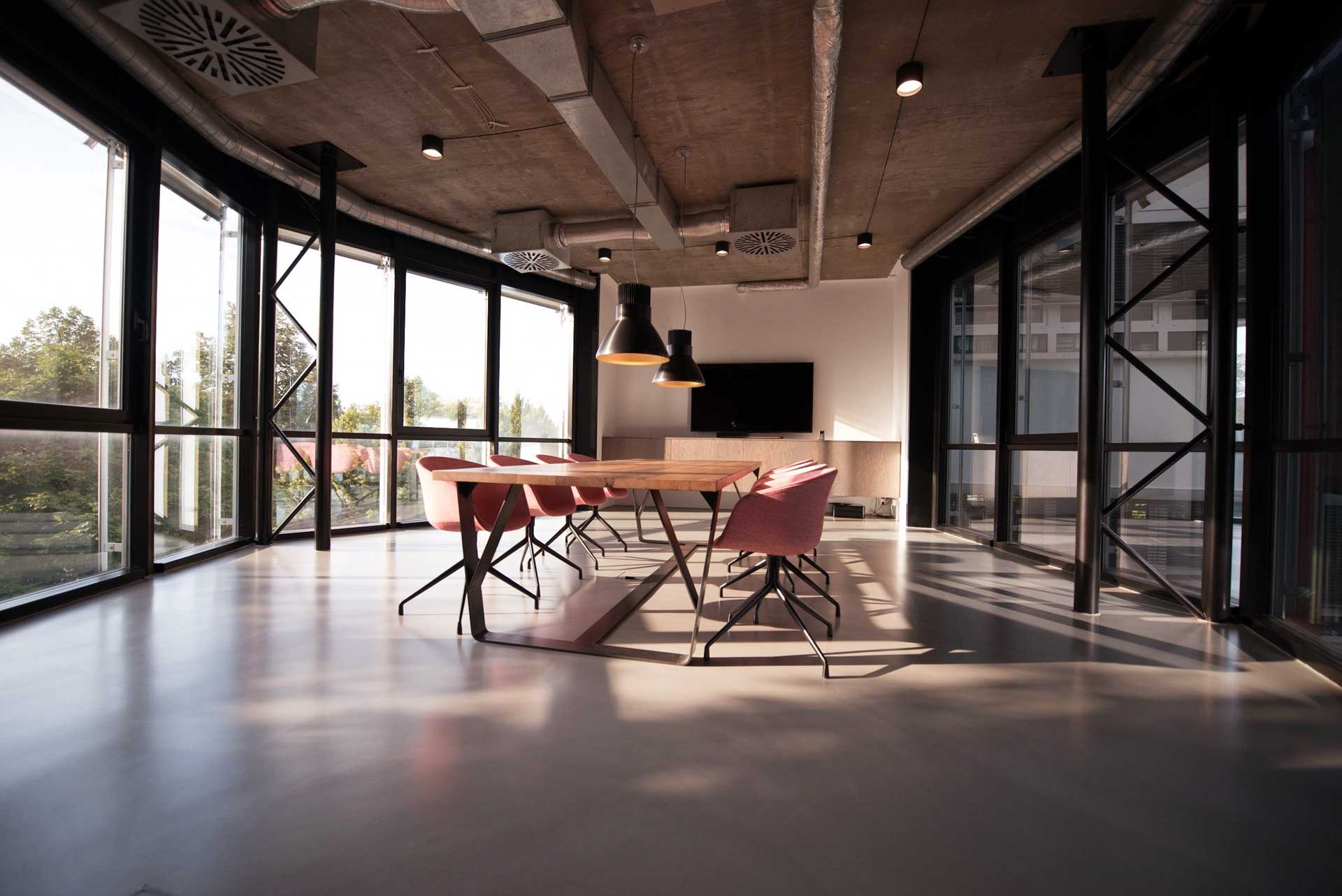 large office filled with sunlight and meeting table in the middle