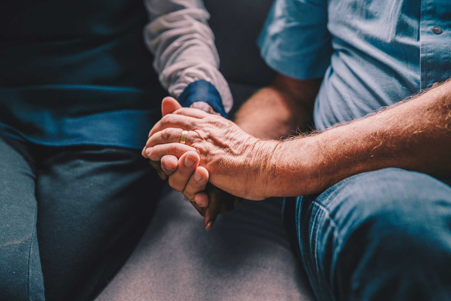 older man and woman holding hands while sitting