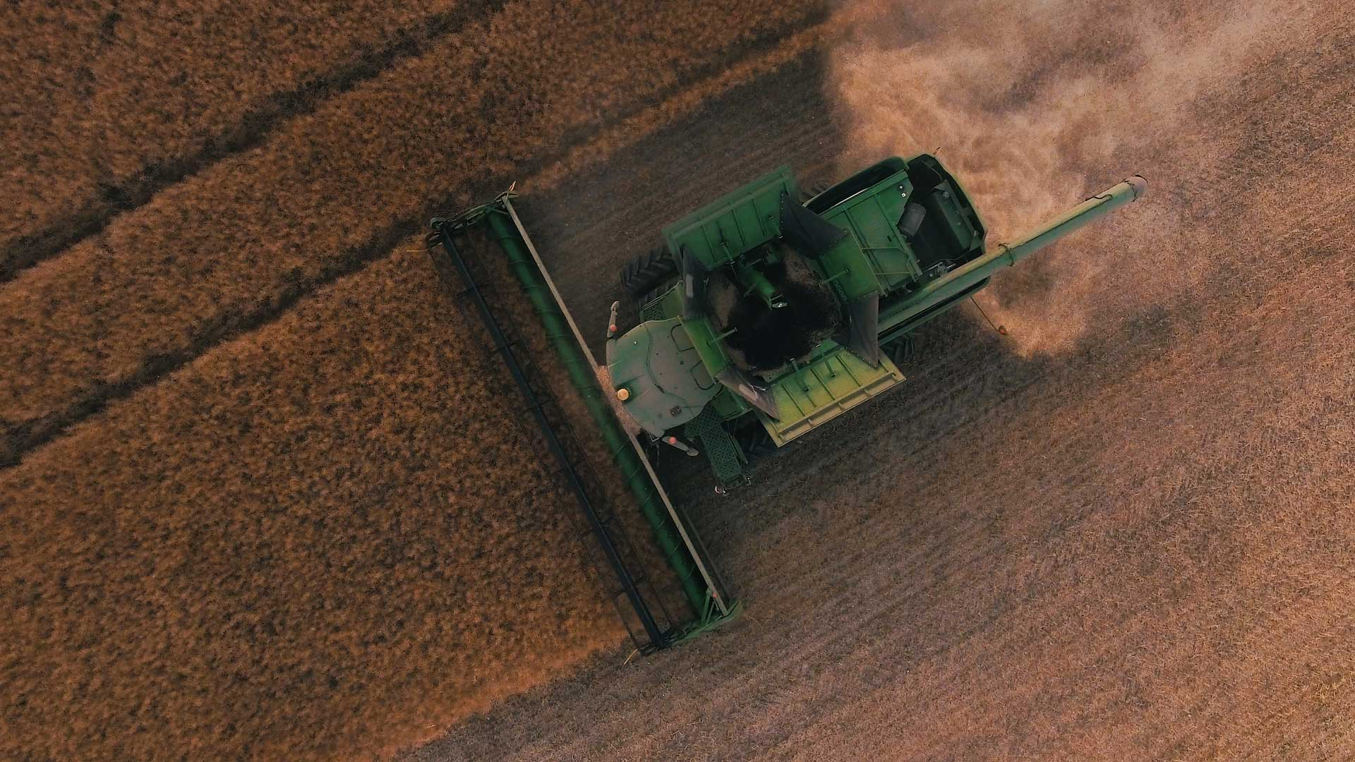 show of farm tractor mowing fields on farm from above