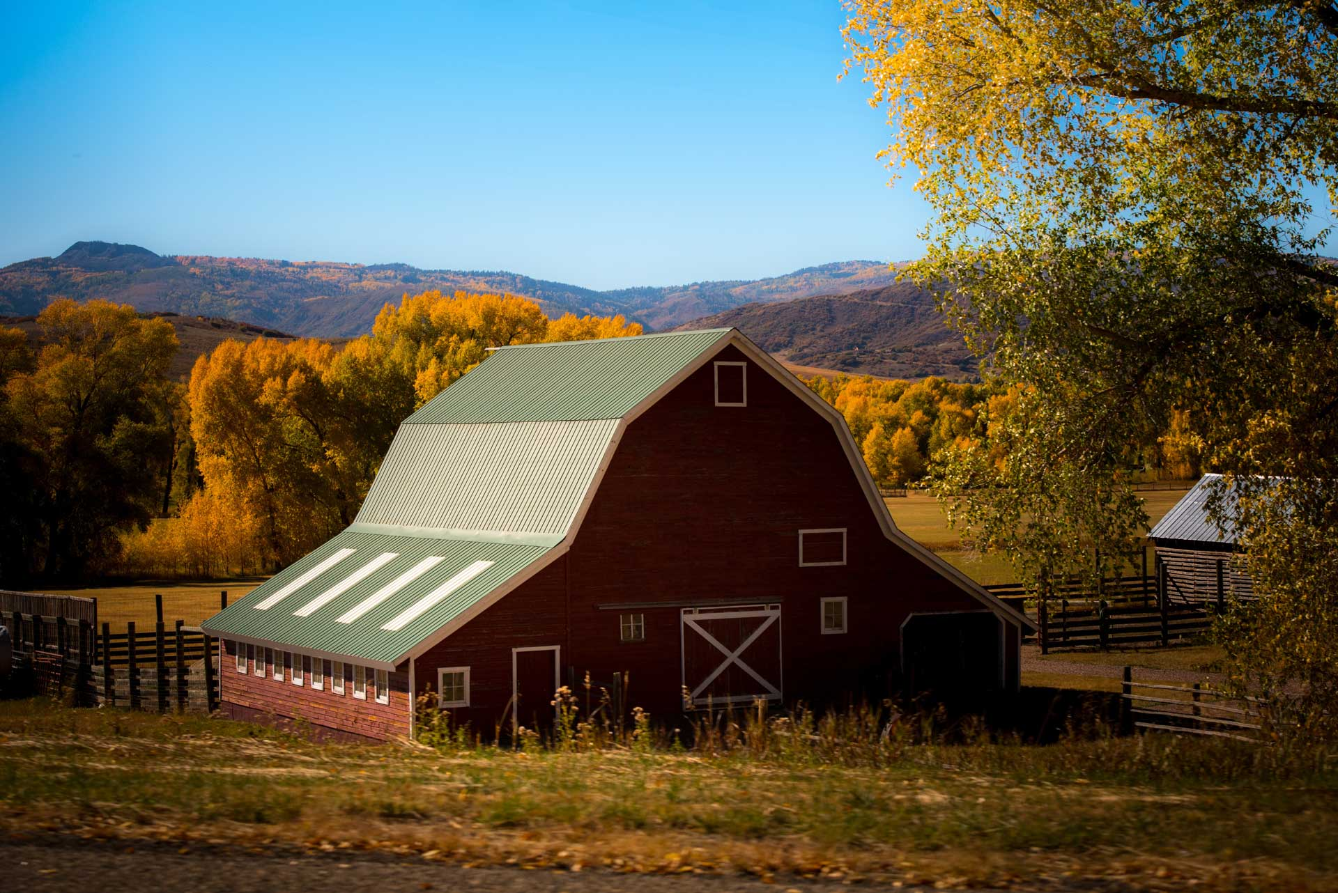 red barn with green roof surrounded with trees in the distance during fall
